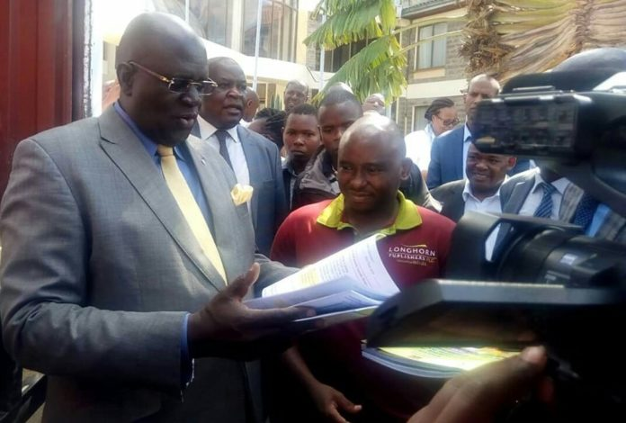 Photo- Education CS, Prof George Magoha, peruses through a book for the new curriculum at the Kenya Institute of Curriculum Development, KICD, in Nairobi on Sunday 28th April, 2019. The CS flagged off the distribution of 12,360,000 new Curriculum textbooks to schools.