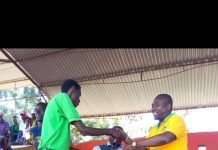 This is for you. Kisii County KUPPET Executive Secretary Omari Otungu (Left) donates a track suit to Nyanchwa Boys' Basketball Team Coach, Kefa Mogire, after retaining his Kisii County trophy on Saturday.